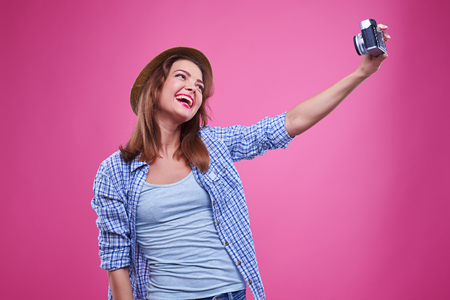 exhilarated: Mid shot of exhilarated woman smiling while making selfie photo. Stock Photo