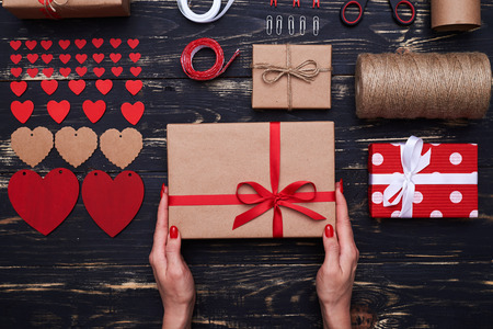 High angle of arranged decorative stuff with a gift box in hands. Stock Photo