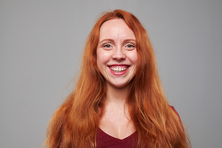 red hair girl: Close-up of grinning red hair girl isolated in studio. Standing and posing at the camera Stock Photo