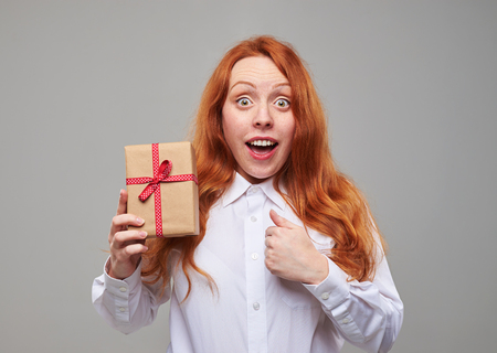 red hair girl: Close-up of sensitive red hair girl holding a present box isolated over background. Posing at the camera  with a gift box