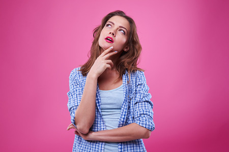 preoccupied: Studio shot of preoccupied girl looking upwards and making decision. Isolated over pink background