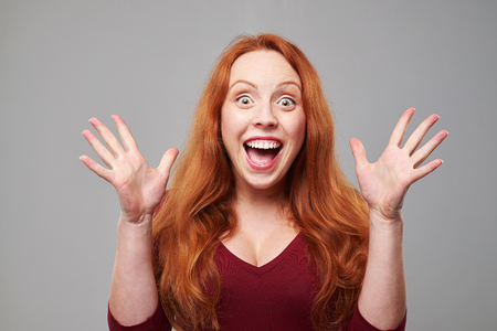 facial expression: Close-up portrait of young red hair woman with facial expression of surprise. Raised hands isolated over background
