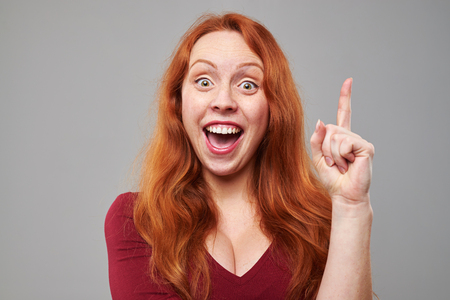 exhilarated: Close-up of exhilarated woman with raised index finger coming up with idea. Woman isolated over gray background