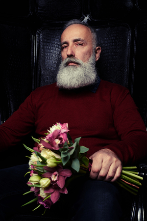 males only: Close-up shot of a severe bearded man in black sitting in an armchair with a bouquet of flowers. The concept of congratulation, holiday