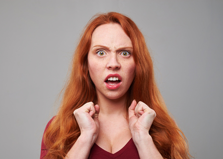Close-up portrait of red hair woman making a disgusted expression. Negative human emotion face expression Фото со стока
