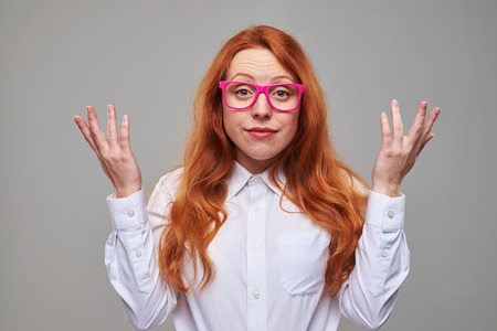 pelo rojo: Close-up of frustrated red hair student in pink glasses isolated over background in the studio. Exhausted girl looking tired Foto de archivo