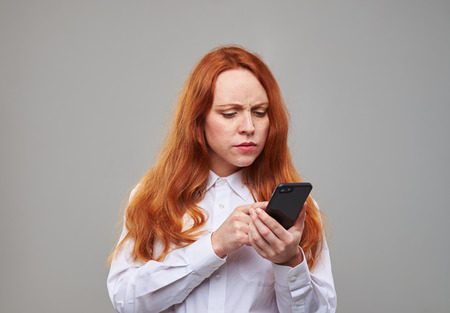 mobile telephone: Close-up of confused girl looking attentively at the screen of mobile telephone. Red hair girl posing at the studio with a smartphone Stock Photo