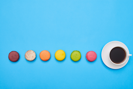 Stretch of macaroons with a cup of coffee in the end with a copy space