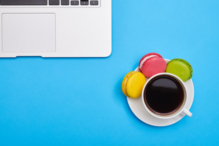 Top view image of a coffee with delicious macaroons and laptop over blue flatlay Stock Photo
