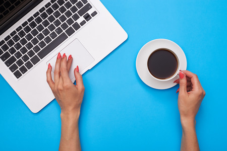High angle of a woman hand holding a cup of coffee over blue flatlay. Hand holding a cup of coffee while putting hand on a touchpad of the laptop
