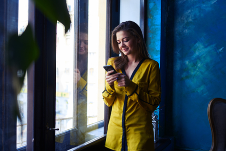mobile telephone: Close-up shot of a stylish modern woman standing with mobile telephone near the window. Smiling while chatting with someone. Using telephone Stock Photo