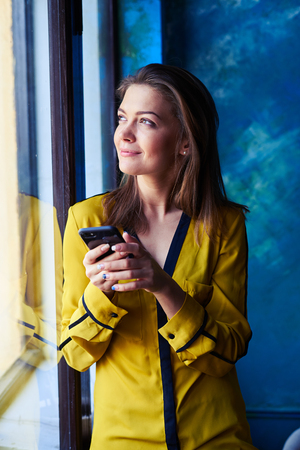 mobile telephone: Close-up shot of a dreamy young girl looking through the window while using telephone. Sunrays penetrate through the window. Woman with mobile phone next to the window Stock Photo