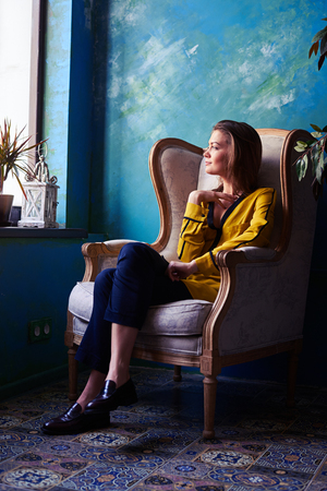 Low angle of a delightful young girl looking through the window while dreaming about something. Female in a yellow blouse looking sideward Stock Photo