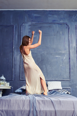 woman in bed: Back view of a woman dancing with raised hands on the bed. Elated female having fun early in the morning. Woman wearing a long nightgown standing on the bed Stock Photo