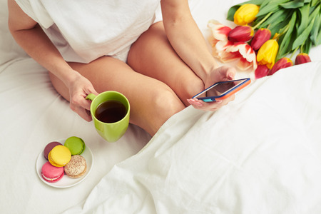 Overhead shot of female using telephone while lying in the bed. Bared legs female drinking tea with macaroons in the bed
