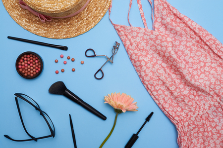 Top view of female clothes and accessories on blue background. Summer accessories collage with cosmetics
