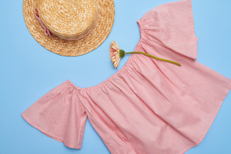 Overhead shot of an off-the-shoulder swing blouse with straw hat. Summer feminine outfit. Straw hat, blouse and flower on blue Stock Photo