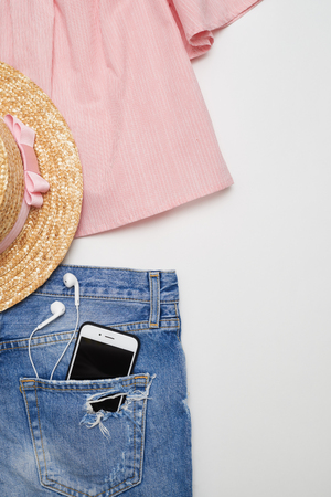 feminine background: Overhead shot of feminine clothes and accessories collage of ripped denim jeans, blouse, telephone and headphones on white background