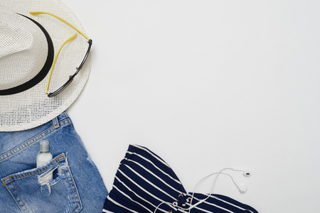 Top view shot of denim shorts, stripped top, straw hat and headphones lying on a white background. Sunglasses and cream in the pocket. Summer clothes collection