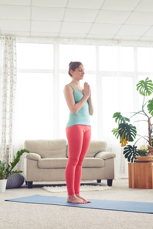 sport clothes: Side view of pretty woman meditating on yoga mat indoor. Wearing comfortable sport clothes Stock Photo
