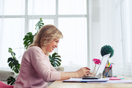 Side view of smiling madam working in laptop in bright room