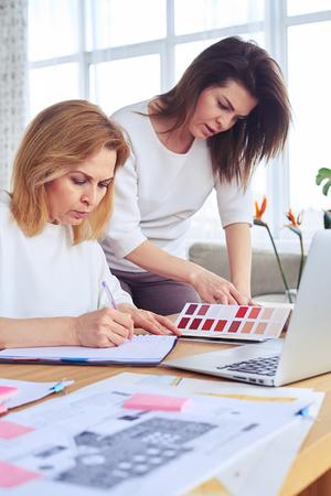Vue latérale de deux madames très sérieuses regardant à travers le catalogue de la palette de couleurs Banque d'images - 78152145