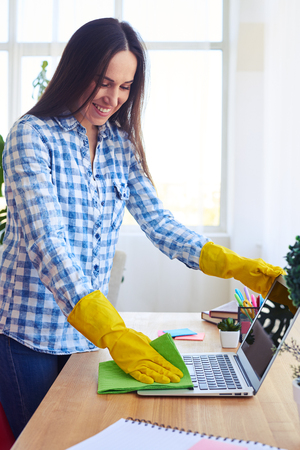 Vertical of smiling brunette in shirt and gloves dusting laptop Stock Photo