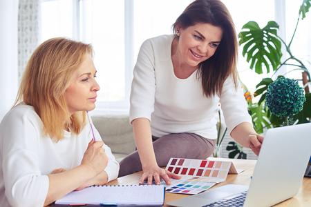 Gros plan de madames heureuses travaillant avec catalogue de palette de couleurs et ordinateur portable Banque d'images - 78163769