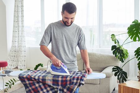 Mid shot of pleasant gentleman ironing attentively shirt on ironing board