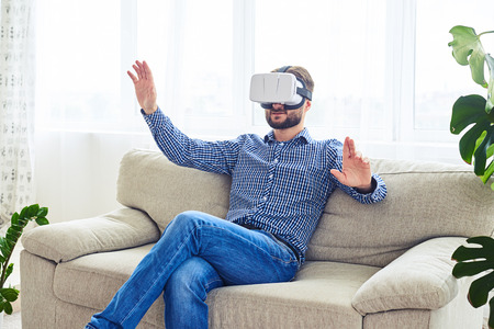 work from home: Wide shot of stylish male with beard working in VR glasses sitting on sofa