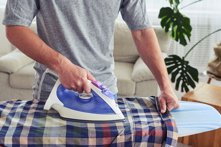 work from home: Cropped shot of muscular male ironing attentively shirt on ironing board Stock Photo