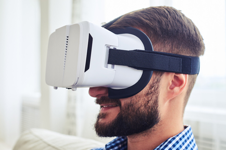 one mature man only: Close-up of mature male with beard working in VR glasses sitting on sofa