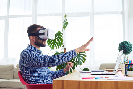 Mid shot of male in virtual reality glasses orienting in space sitting at table Stock Photo