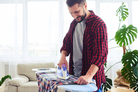 Mid shot of handsome man ironing attentively clothes on ironing board