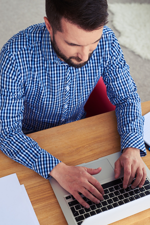 work from home: High-angled shot of busy male working in laptop while sitting in red armchair Stock Photo