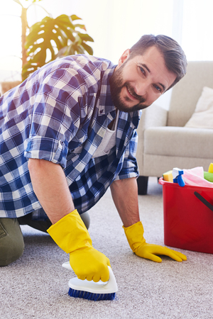 Vertical of hardworking sir in gloves brushing carpet in spacy room Stock Photo