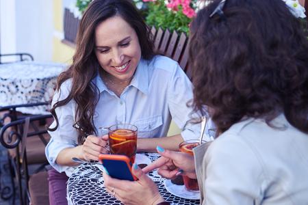 Gros plan, de, madames, joyeux, surfer sur, internet, sur, tasse thé, sur, terrasse Banque d'images - 79548478