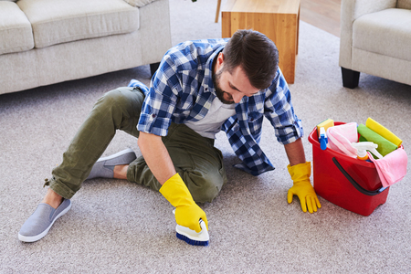 Wide shot of attentive gentleman in gloves brushing carpet while sitting Stock Photo