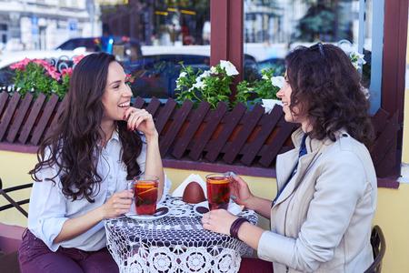 Coup milieu de merveilleuses madames qui communiquent et boivent du thé pendant la pause Banque d'images - 79548488