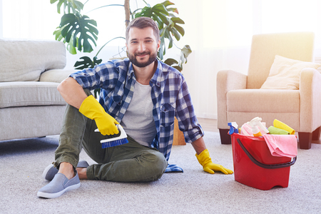 manpower: Wide shot of caring male in gloves having rest while brushing carpet with copy space