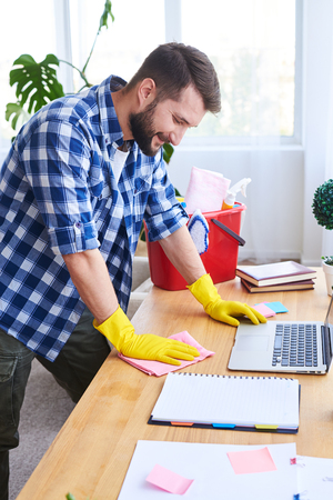 Vertical of good-looking sir mopping work place in bright room