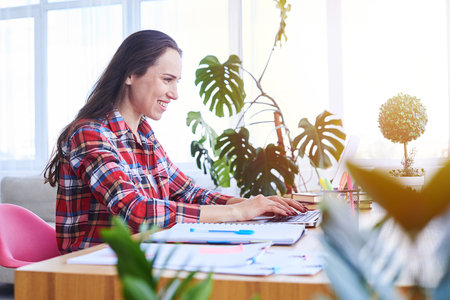Wide shot of concentrated madam working in laptop while sitting in desk in sunny room Stock Photo