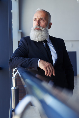 concentrate: Vertical of serious sir age of 50-60 looking out window Stock Photo