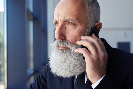 Close-up of thoughtful male talking on phone while looking out window