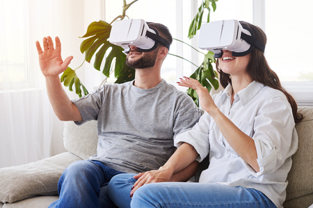 Mid shot of couple in VR glasses holding hands and orienting in space Stock Photo