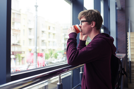 Mid shot of boy in glasses drinking coffee and talking on phone while leading on handrail and looking out window