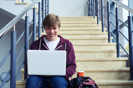 break from work: Wide shot of handsome guy chatting in laptop while sitting on stairs with copy space Stock Photo
