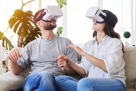 Mid shot of good-looking pair in VR goggles holding hands and orienting in space Stock Photo