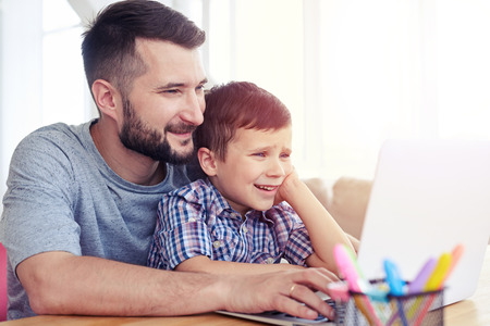 Close-up shot of father and son using laptop on table at home. Familly spending time together Banco de Imagens - 80181784