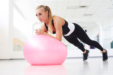 Low angle view of focused attractive woman in tracksuit doing stretching exercises on pink fitball Stock Photo